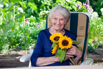 Happy Old Lady Sitting on Chair Holding Sunflowers.