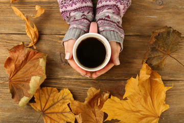 Female hand holding cups of coffee with autumn leaves on rustic wooden table background
