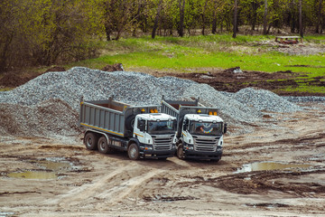 two dump trucks on a construction site