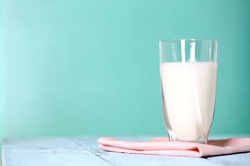 Glass of milk on wooden table on blue background