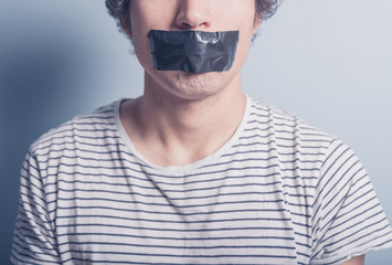 Young man with tape covering his mouth