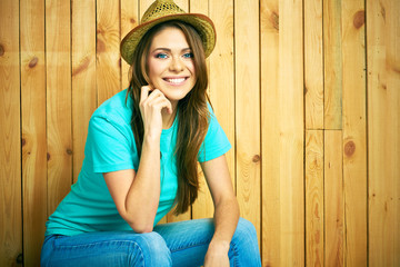 Teenager girl smiling with teeth seating against wood backgroun