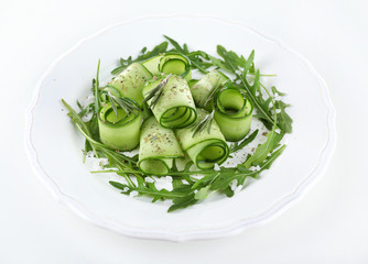 Plate of green salad with cucumber, arugula and rosemary