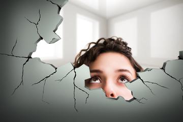 junge brünette Frau schaut durch großes Loch in der Wand