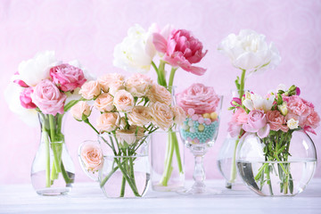 Beautiful spring flowers in glass vases on light pink