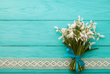 Bouquet of snowdrops with lace ribbon on wooden background