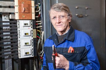Electrician with pliers in hands stands near high voltage panel