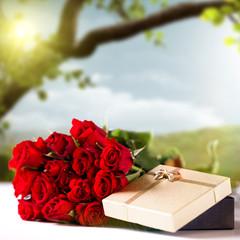 Rosen und Geschenkbox vor Frühlingshintergrund