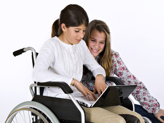 Girl sat in a wheelchair studying with a friend with a computer