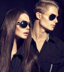Fashion models couple wearing sunglasses over dark background