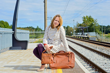 Woman sitting with brown bag and suitcase