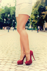 woman legs in red high heel shoes and shorts outdoor shot