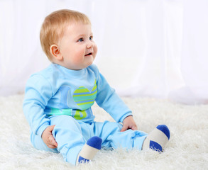 Cute baby boy on carpet, on light background