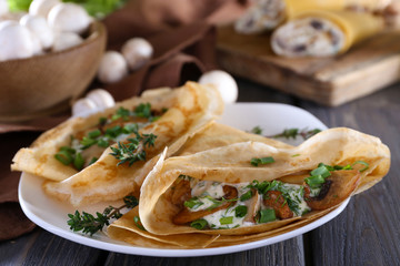Pancakes with creamy mushrooms in plate on wooden table,