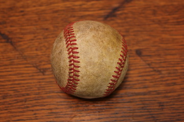 Worn out baseball on wood