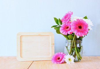 Summer bouquet of flowers on the wooden table and wooden board w