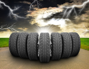 Wedge of car wheels. Road, roadsides, grass field and stormy sky