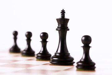 Black chess pieces on a chessboard isolated