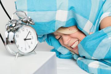 Junge Frau liegt schlaflos im Bett