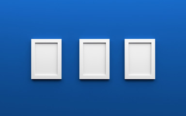 Composition of three white blank photo frames on blue wall