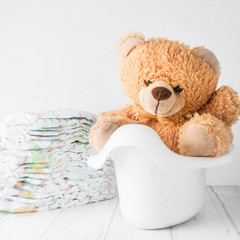 A teddy bear in a white potty next to stack of diapers
