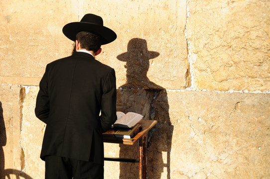 Religious orthodox jew praying at the Western wall in Jerusalem.