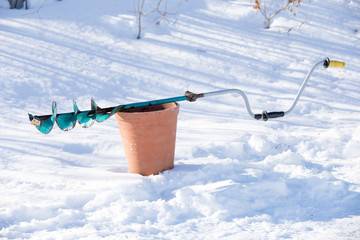 drill for ice fishing lie on bucket