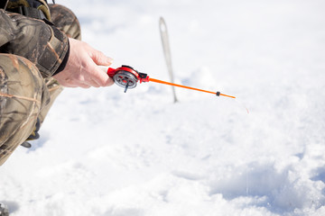 small rod for ice fishing in  hands near  hole