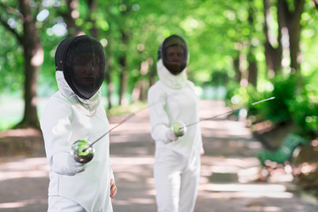 Two rapier fencers women staying in park alley getting ready for