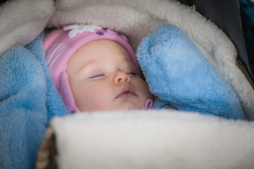 Sleeping baby lying in the stroller. Peaceful infant girl
