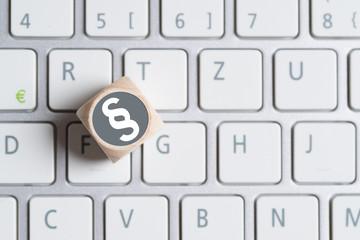 Würfel mit Paragraph Symbol auf einer Tastatur