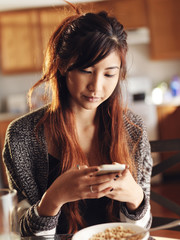 asian girl using smart phone in kitchen at breakfast