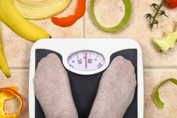 Feet on bathroom scale with fruit peals around