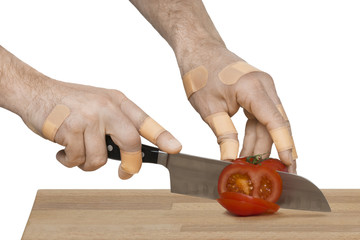 Injured hands with knife cutting a tomato