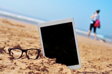 eyeglasses and tablet with black blank space in the screen, in t