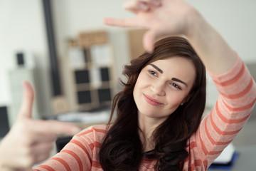 lächelnde frau formt einen rahmen mit den händen