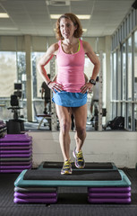 muscular woman doing step aerobics