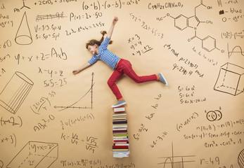 Cute girl learning playfully in frot of a big blackboard