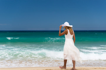 Young woman in white dress and hat is walking on the beach