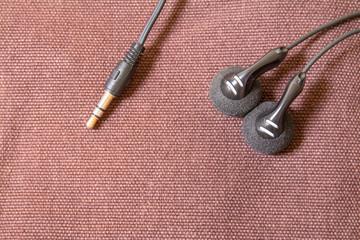 black earbud on brown canvas bag