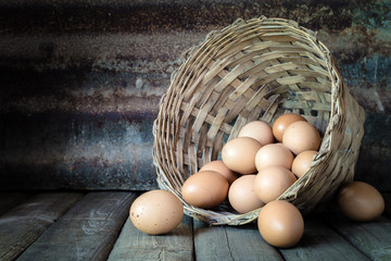 still life with eggs in bamboo basket on wood table and rusty st