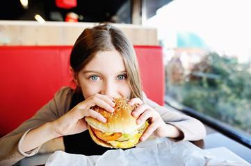 Cute little  girl eating a hamburger