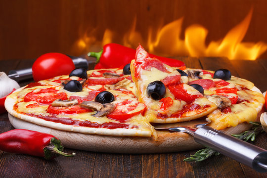 Baked hot pizza with one slice on lifter with fire on background
