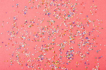 Fototapete - Colorful round sprinkles spilled on red background, isolated