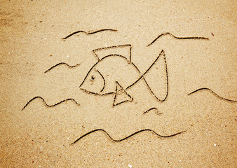 A fish symbol in drawn in the sand