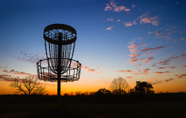 Silhouette of disc golf basket in the park at sunset
