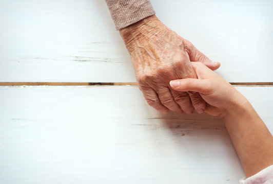 Unrecognizable grandmother and granddaughter holding hands