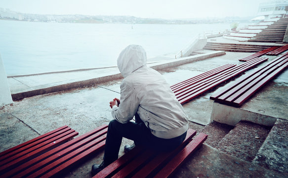 young man sitting on the promenade on a cloudy day