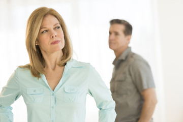 Angry Woman Looking Away With Man In Background At Home