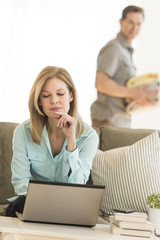 Mature Woman Using Laptop While Man In Background At Home